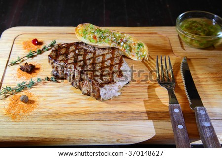 Beef steak medium rare. Beef steak on wooden plate plate - Stock Image