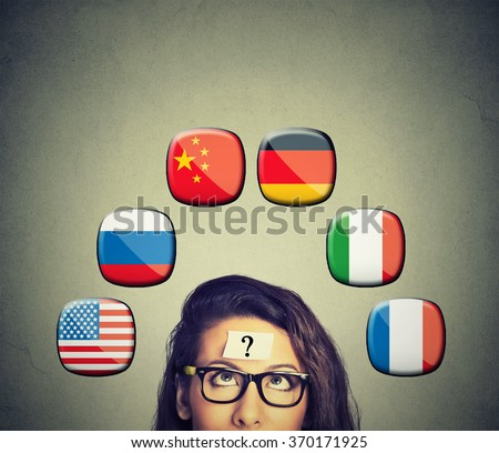 Work and travel immigration opportunity concept. Foreign language studying process. Woman with question mark and icons of international flags above head isolated on gray wall background. Royalty-Free Stock Photo #370171925