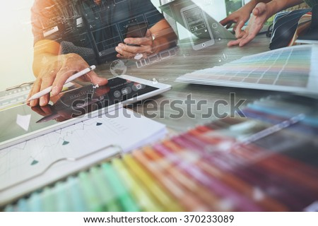 two colleagues interior designer discussing data and digital tablet and computer laptop with sample material and graphics design diagram on wooden desk as concept