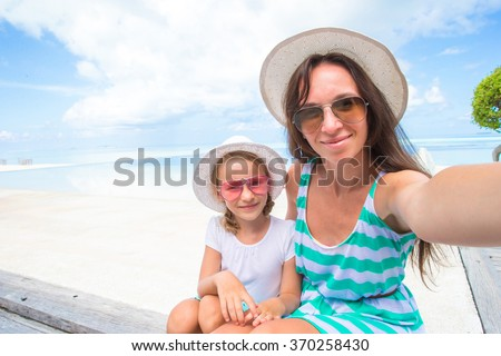 Mother and little girl taking self portrait at tropical vacation