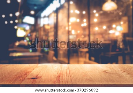 Wood table  on blur bokeh cafe or restaurant background(in night) .For product display template
