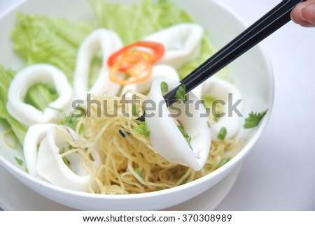 Stir fried egg noodles with cooked quid, Vietnamese cuisine.  This will be eaten along with a bowl of soup.  #370308989