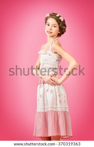 Portrait of a beautiful girl with braided hair wearing summer sundress. Children fashion.  #370319363