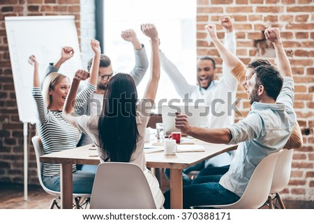 We did it! Group of six cheerful young people keeping arms outstretched and smiling while sitting at the table in office  #370388171