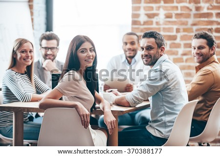 Perfect team. Group of six cheerful young people looking at camera with smile while sitting at the table in office  #370388177