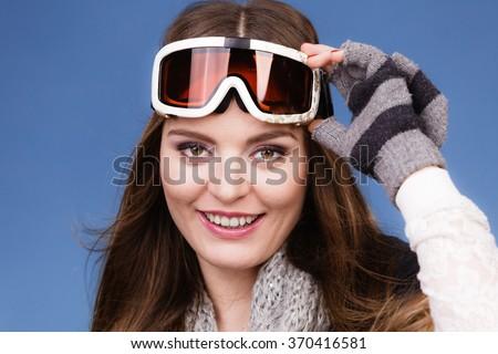 Woman skier girl wearing warm clothing ski goggles portrait. Winter sport activity. Beautiful sportswoman on blue studio shot #370416581