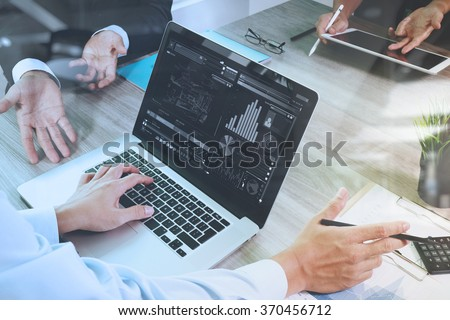 business documents on office table with smart phone and laptop computer and graph financial with social network diagram and three colleagues discussing data in the background Royalty-Free Stock Photo #370456712
