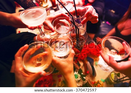 Clinking glasses with alcohol and toasting, party Royalty-Free Stock Photo #370472597