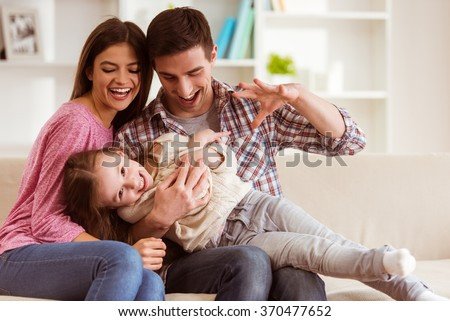 Smiling young parents and their child are very happy, they are at home #370477652