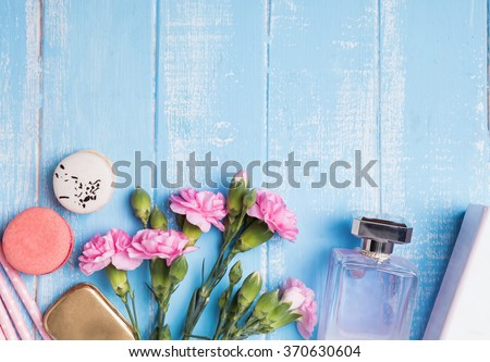 Perfume, flowers, macarons and boxes on blue colored table, top view