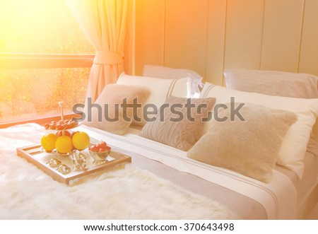 wooden tray with fresh fruits on cozy bed in hotel #370643498