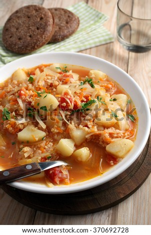 Traditional Polish soup kapusnyak on a rustic table #370692728