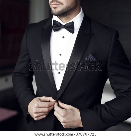 Sexy man in tuxedo and bow tie posing #370707923