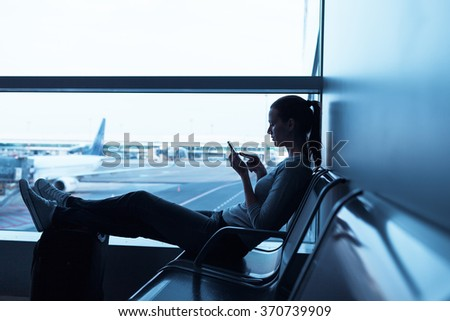 Woman waiting in airport terminal using her smartphone Royalty-Free Stock Photo #370739909