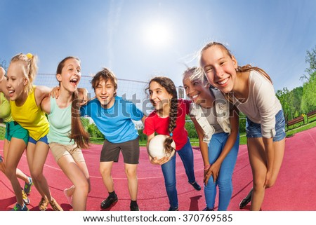 Happy teens standing on the volleyball game court #370769585
