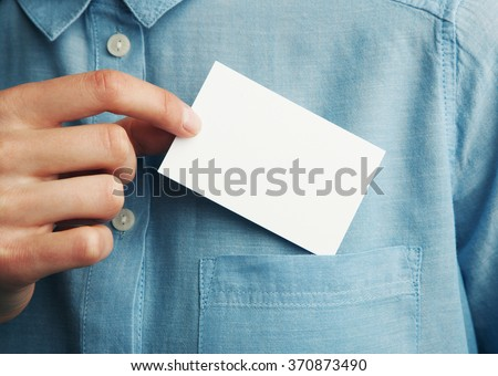 Young man who takes out blank business card from the pocket of his shirt