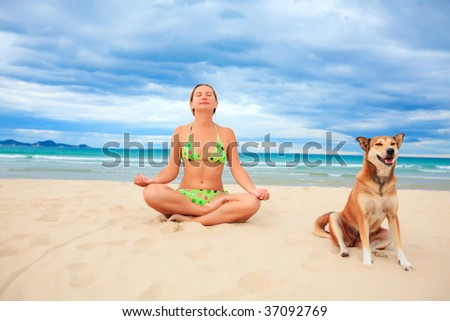 Woman with dog are meditating on the tropical beach #37092769