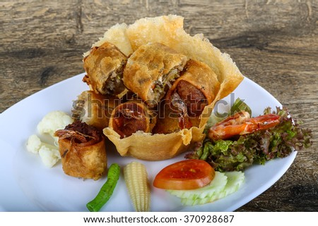Fried spring rolls in eatable basket with salad leaves #370928687