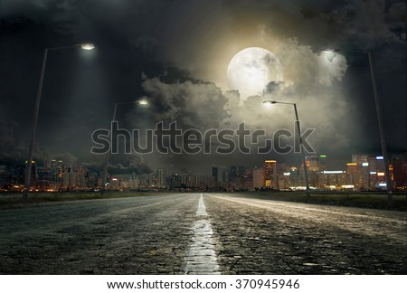 asphalt road leading into the city at night #370945946
