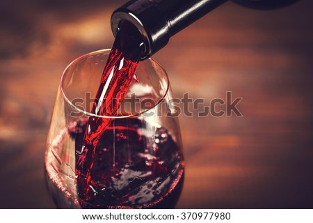 Pouring red wine into the glass against wooden background Royalty-Free Stock Photo #370977980