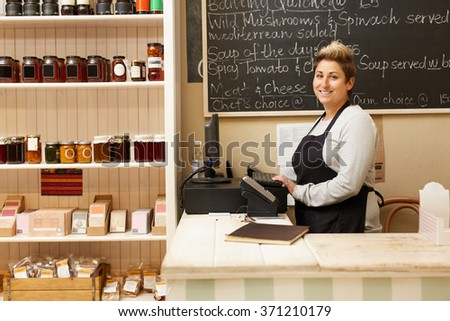 A young deli worker standing behind the counter #371210179