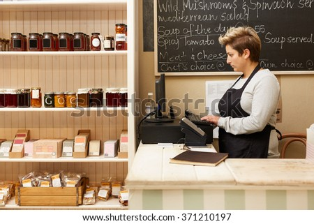 A young deli worker standing behind the counter #371210197