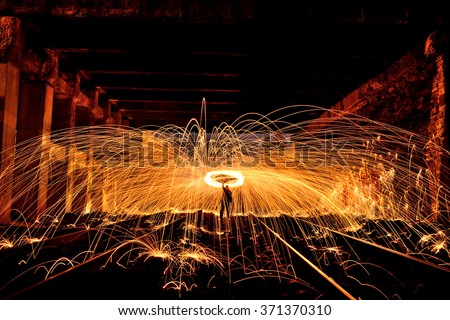 Burning steel wool spinned in urban area. Showers of glowing sparks from spinning steel wool. Man in the fire. (Night photo without effects with little noise)