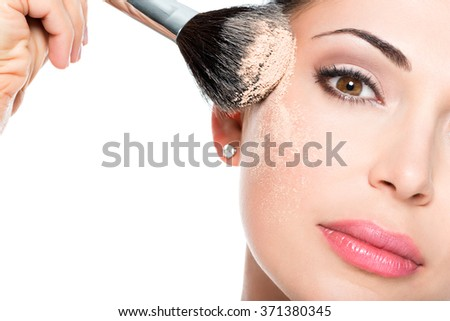 Closeup portrait of a woman  applying dry cosmetic tonal foundation  on the face using makeup brush.  #371380345