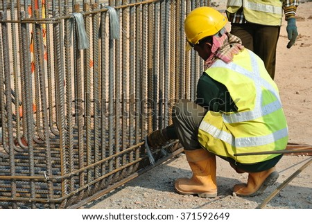 SELANGOR, MALAYSIA â?? SEPTEMBER 03, 2015: Group of construction workers fabricating pile cap steel reinforcement bar at the construction site.   #371592649