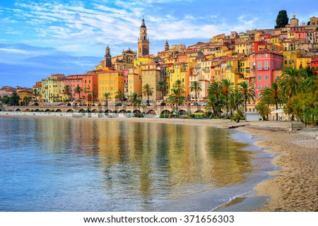 Sand beach beneath the colorful old town Menton on french Riviera, France Royalty-Free Stock Photo #371656303