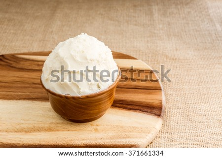 Unrefined, organic Shea butter in the wooden bowl, stands on the wooden board, jute fabric background. #371661334