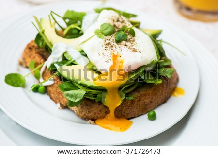 Healthy Breakfast with Wholemeal Bread Toast and Poached Egg with Green Salad, Avocado and Peas. Orange Juice and Orange Slices on the Background. #371726473
