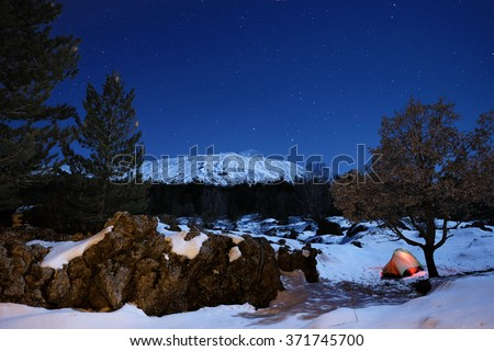 rock formation 'sciara' and lighting tent in the snow of Etna Park under starry sky, Sicily  #371745700