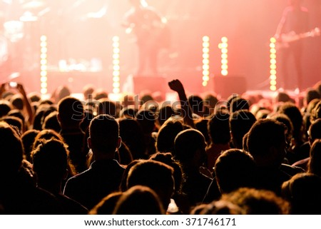 Silhouettes of concert crowd in front of bright stage lights Royalty-Free Stock Photo #371746171