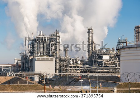 oil refinery with smoking chimneys against blue sky #371895754