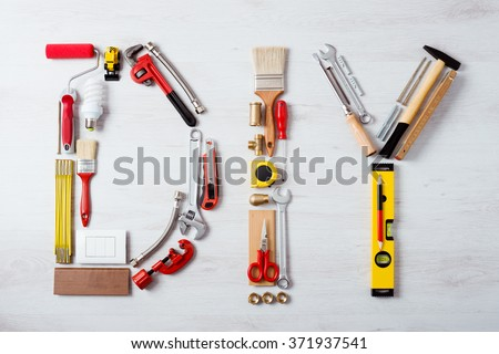 DIY word composed of work and construction tools on a wooden surface top view, hobby and craft concept Royalty-Free Stock Photo #371937541