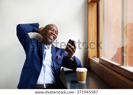 Portrait of smiling businessman sitting at a cafe looking at mobile phone #371945587