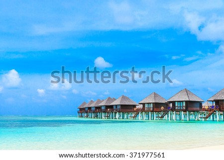 tropical beach in Maldives with few palm trees and blue lagoon #371977561