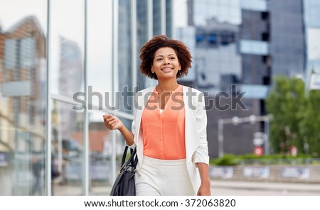 happy young african american businesswoman in city #372063820
