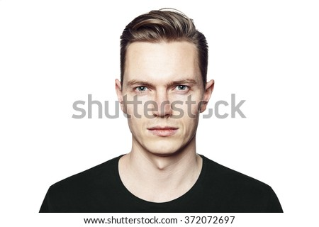 Studio shot of young man looking at the camera. Isolated on white background. Horizontal format, he has a serious face, he is wearing a black T-shirt. #372072697