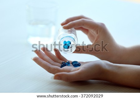 Woman spills blue medical capsules  to her hand, close up #372092029