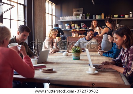Interior Of Coffee Shop With Customers Using Digital Devices Royalty-Free Stock Photo #372378982