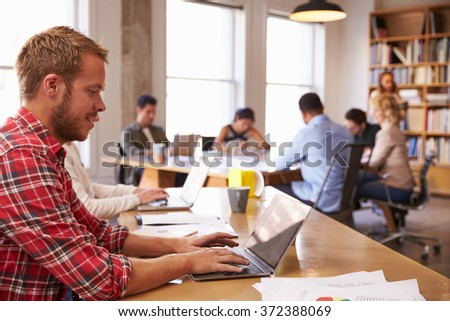 Businessman Using Laptop At Desk In Busy Office #372388069