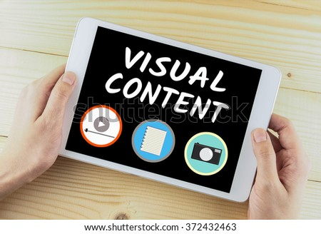 tablet in hand on wooden desk word visual content