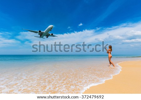 Beautiful sea and sky with a woman in bikini is taking photo of airplane that about to landing by her mobile phone, Phuket, Thailand.