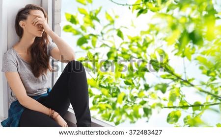 sad pretty teenage girl sitting on windowsill Royalty-Free Stock Photo #372483427