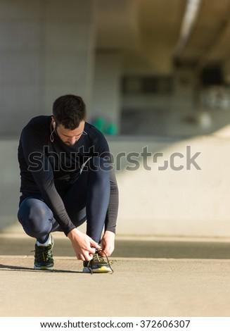 Urban jogger tying his running shoes on a big bridge. #372606307
