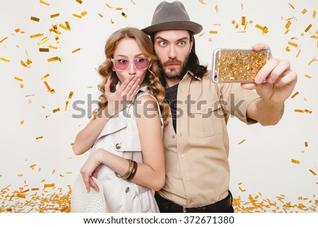 young stylish hipster couple in love making self photo, celebrating disco party, having fun, amazed, exited, funny face, golden confetti, holding phone, trendy apparel, cruise style, white background