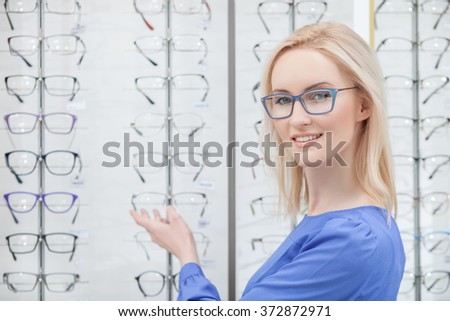 Beautiful blond girl wants to buy eyeglasses #372872971