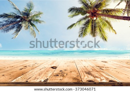 Top of wood table with blurred sea and coconut tree background - Empty ready for your product display montage. Concept of beach in summer #373046071